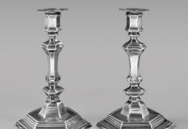 84 - Paire de FLAMBEAUX en argent, à base hexagonale chantournée, à gorge et à doucine, l'ombilic ceinturé d'un fil plat, surmonté du fût triangulaire à pans coupés, entre deux noeuds, le plus bas, à enroulement, le binet, également à pans, Maître Orfèvre Jean-Baptiste NAVIER, reçu en 1712, PERPIGNAN vers1720-1725, gravés sur le pied de la lettre A entre deux fleurons (marque du commanditaire ?), les bobèches rapportées ultérieurement, également en argent Poids 1,245 kg – Hauteur 25 cm Jean-Baptiste NAVIER est reçu le 13 mai 1712, insculpant son poinçon à l'atelier monétaire, tout juste créé en 1710 et investi du pouvoir de contrôle. Il se marie le lendemain avec la fille d'un orfèvre, que l'on appelait, encore, « argenter ». Il occupe la fonction d'essayeur à la Monnaie de PERPIGNAN de 1716 à 1763. Il décède en 1767. On trouve dans ses oeuvres répertoriées, plusieurs calices pour les églises de BANYULS, MONTALBA, PERPIGNEN ou RODÈS. Bibliographie : Louis AUSSEIL « L'Orfèvrerie du ROUSSILLON -,Les Orfèvres de la Juridiction de PERPIGNAN du XIII° au XIX° siècle » - Conseil général, Directions des Archives départementales, PERPIGNAN 1994.